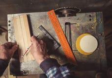 老木匠与木头一起使用 免版税库存照片