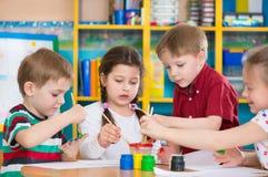 画与五颜六色的油漆的逗人喜爱的孩子在幼儿园 库存图片