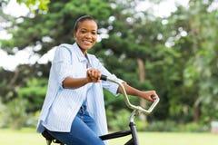 美国黑人的妇女骑马自行车在森林里 库存照片