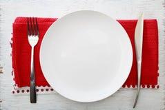 Άσπρο πιάτο με το δίκρανο και το μαχαίρι Στοκ Φωτογραφίες