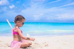 有翼的可爱的小女孩喜欢蝴蝶海滩假期 免版税库存照片