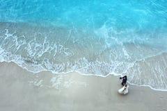 白色沙子海滩和大海与美好的新娘和新郎可爱的夫妇 免版税库存图片