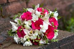 兰花和玫瑰的白色和红颜色花花束婚礼的 免版税库存图片