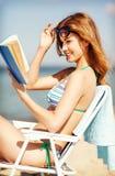 女孩在海滩睡椅的阅读书 图库摄影