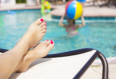 美丽的脚和脚趾由游泳池 库存图片