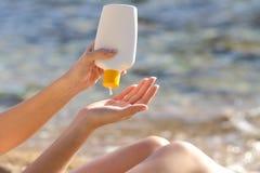 妇女递把从瓶的遮光剂放在海滩上 免版税库存图片