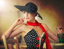有坐在餐馆的黑帽会议和红色围巾的可爱的夫人 免版税库存照片