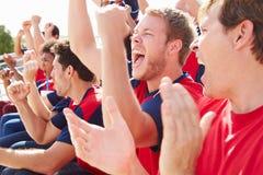 Зрители в цветах команды наблюдая событие спорт Стоковая Фотография