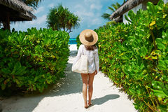 Женщина при шляпа сумки и солнца идя пристать к берегу Стоковые Фото