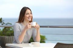 拿着一杯咖啡的美丽的妇女在餐馆 免版税库存图片