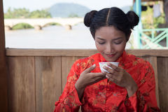 亚裔女孩品尝从杯子的饮料 免版税库存照片