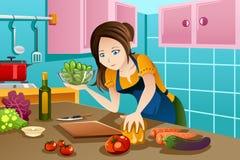 烹调健康食物的妇女在厨房里 免版税库存照片