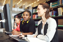 学习在有计算机的图书馆里的大学生 免版税库存照片