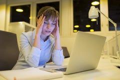 后工作在办公室的被注重的女实业家 免版税库存照片