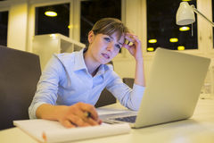 后工作在办公室的被注重的女实业家 库存图片