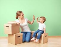 愉快的家庭母亲和小女儿一栋空的公寓的与 免版税库存图片