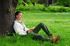 在自然的年轻愉快的人阅读书 免版税库存照片
