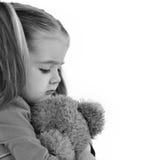 拿着玩具熊的哀伤的小孩 免版税库存图片