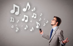 唱歌和听到与音乐会的音乐的可爱的年轻人 免版税图库摄影