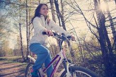 有山自行车的美丽的少妇 免版税库存照片