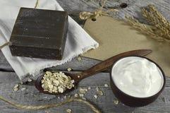 与黑肥皂、奶油和燕麦的静物画 免版税图库摄影