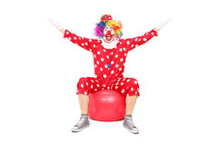 极度高兴的小丑坐健身球 免版税库存图片