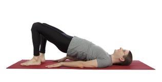 做在瑜伽的人桥梁姿势 库存图片