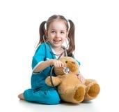 有医生审查的玩具熊衣裳的孩子  免版税库存照片