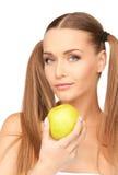 年轻美丽的妇女用绿色苹果 免版税库存照片