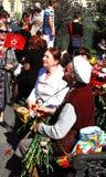 妇女接受花的退役军人,她微笑 库存照片