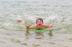 男孩在有他的识别不明飞机委员会的海洋游泳 库存图片