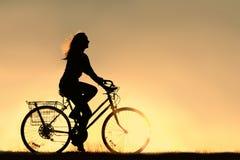 妇女骑马自行车剪影 库存照片