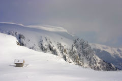 在多雪的山的瑞士山中的牧人小屋 图库摄影