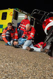 帮助受伤的摩托车司机的紧急队 免版税库存图片
