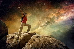 站立在山顶部和享受夜空视图的远足者 库存图片