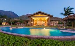 有游泳池的豪华家在日落蓝色 免版税图库摄影