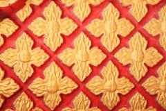 在红色墙壁上的金黄花卉样式 免版税库存照片