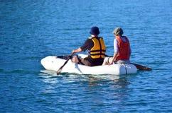夫妇荡桨充气救生艇小船 免版税库存图片