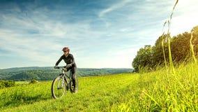 在一个美丽的草甸炫耀自行车妇女,美妙的风景 免版税库存照片