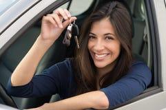 坐在有钥匙的汽车的妇女 免版税库存图片