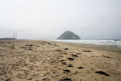 Скала утеса в океане поперек от стогов дыма Стоковые Изображения