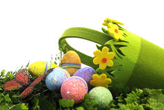 与相当绿色和黄色雏菊篮子的愉快的复活节彩蛋狩猎春天场面用鸡蛋和蝴蝶 库存照片