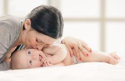 婴孩面颊愉快的亲吻的母亲 库存图片
