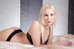 Όμορφη γυναίκα που βρίσκεται στο φωτεινό σατέν Στοκ εικόνα με δικαίωμα ελεύθερης χρήσης
