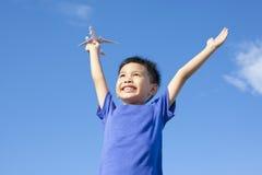 拿着有蓝天的快乐的小男孩一个玩具 免版税库存图片