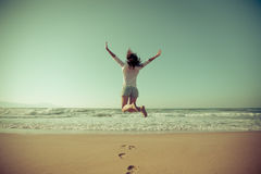 跳跃在海滩的愉快的妇女 库存照片