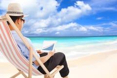商人坐海滩睡椅和看起来储蓄财政 免版税库存图片