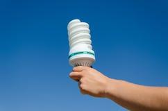 手举行生态在蓝天背景的救球电灯泡 库存图片