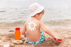 Солнцезащитный крем чертежа солнца на задней части младенца (мальчика) Стоковое Изображение RF