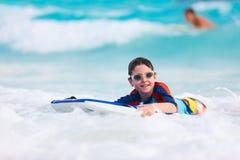 在识别不明飞机委员会的男孩游泳 免版税库存照片